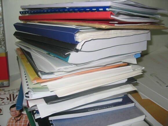 Metáfora de los sesudos planes de empresa tradicionales, con la foto en un montón de documentos apilados